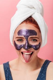 스파 치료를하는 동안 혀를 보여주는 재미있는 여자의 전면 모습. 분홍색 배경에 포즈 얼굴 마스크와 행복 한 여자의 스튜디오 샷.