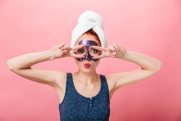 평화 징후를 보여주는 머리에 수건으로 재미있는 여자의 전면 모습. 분홍색 배경에 고립 된 스킨 케어 치료를 하 고 매력적인 여자의 스튜디오 샷.
