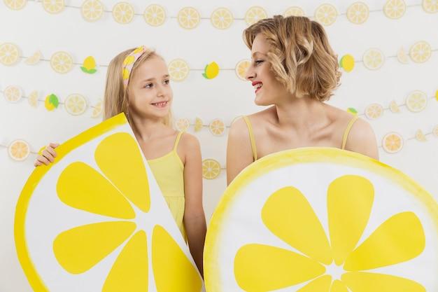 Вид спереди девушка и женщина с лимонными украшениями