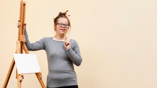 Вид спереди девушки с синдромом дауна позирует рядом с мольбертом
