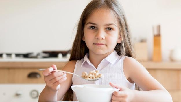 朝食にシリアルを食べる女の子の正面図