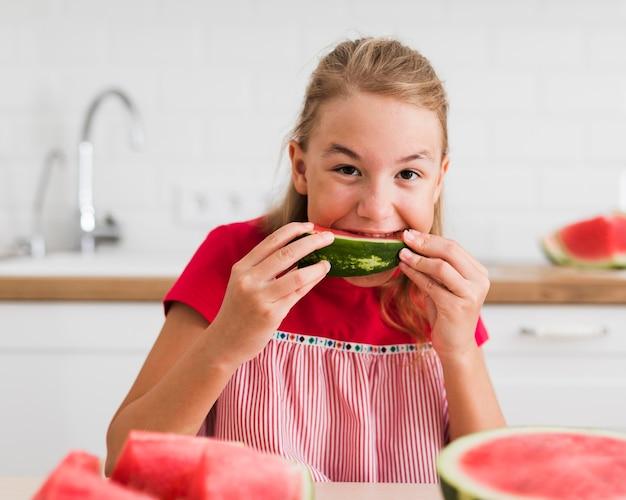 Вид спереди девушки, едящей арбуз