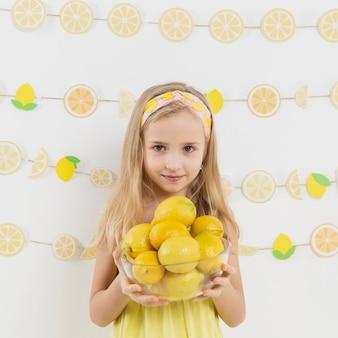 Вид спереди девушка позирует с миской лимонов