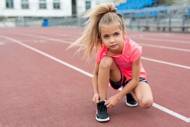 Вид спереди девушки, связывая ее шнурки