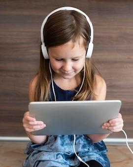 Вид спереди девушки с помощью планшета с наушниками