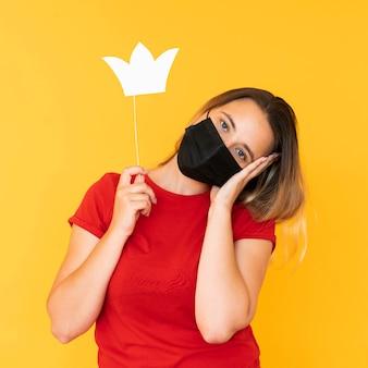 얼굴 마스크와 왕관을 쓰고 여자의 전면보기