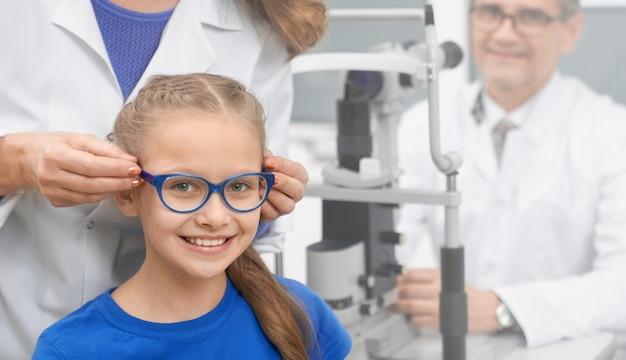 光学ストアで新しい眼鏡をかけている女の子の正面図