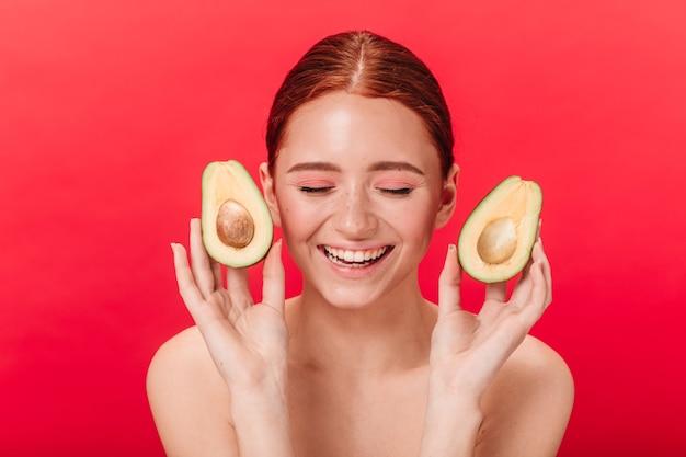 Вид спереди девушки с авокадо, улыбаясь на красном фоне. студия выстрел блаженной женщины смеясь с закрытыми глазами.