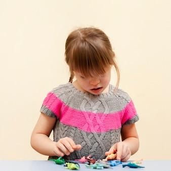 Вид спереди девушки с синдромом дауна и игрушками