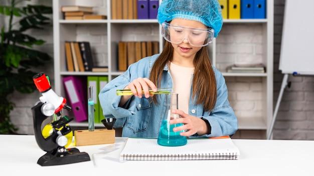 현미경으로 과학 실험을하는 머리카락과 안전 안경 그물을 가진 소녀의 전면보기