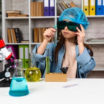 머리 그물과 과학 실험을하는 안전 안경 소녀의 전면보기
