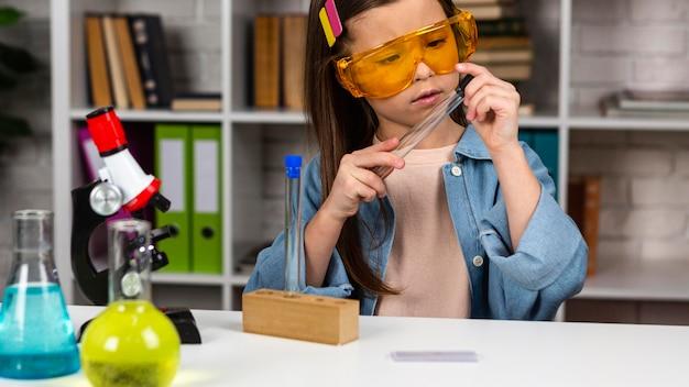Вид спереди девушки с защитными очками и микроскопом