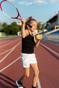 Вид спереди девушки с теннисной ракеткой