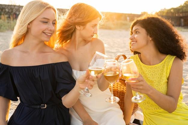 ビーチでワインを飲む女の子の正面図