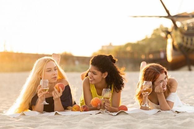 Вид спереди девушек, пьющих вино на пляже