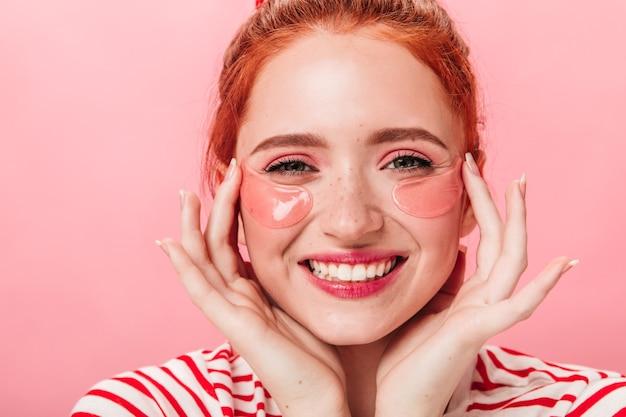 눈 패치 기쁜 유럽 소녀의 전면 모습. 스킨 케어 치료를 하 고 행복 한 생강 여자.