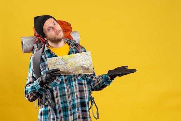 Вид спереди счастливого молодого туриста с кожаными перчатками и рюкзаком, держащего карту
