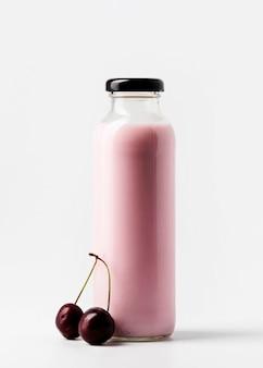Стеклянная бутылка с соком и вишней, вид спереди