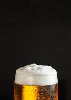 泡とコピースペースとビールのガラスの正面図