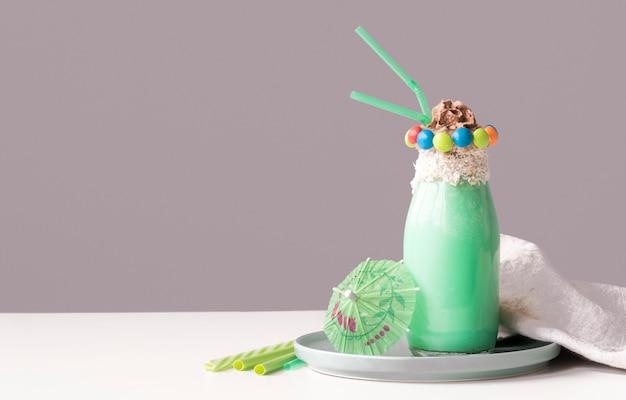 Вид спереди стакан десерта с красочными конфеты сверху и зонтик