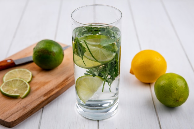 Вид спереди стакана воды с зеленью, лаймом и лимоном на доске с ножом на белой поверхности
