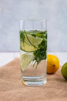 Вид спереди на стакан воды с зеленью и лаймом на бежевой салфетке