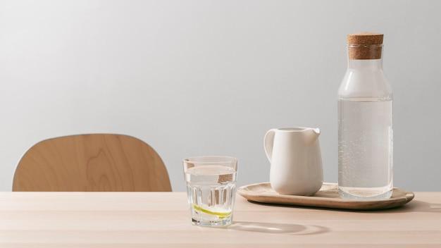 テーブルの上のレモンと水のガラスの正面図