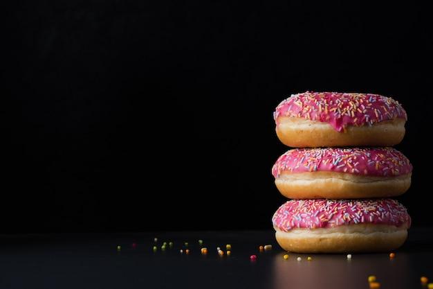 Вид спереди глазированных пончиков сложены с копией пространства