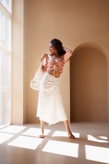 Вид спереди шикарной наполовину африканской молодой модели брюнет нося модные одежды и сандалии лета на пятках.