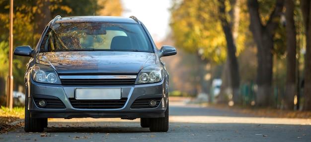 Вид спереди серый блестящий пустой автомобиль на стоянке в тихом районе на широкой аллее под большими деревьями. концепция транспорта и парковки.