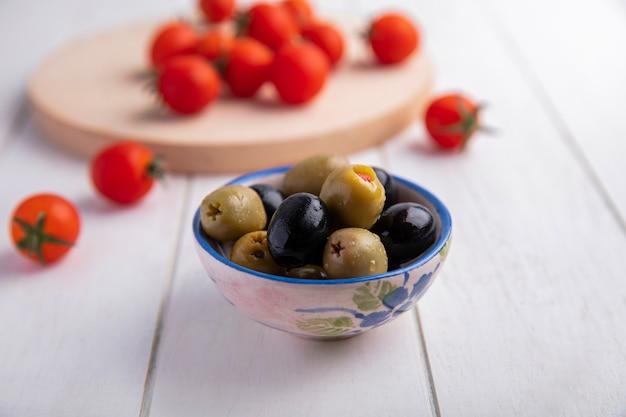 Вид спереди зеленых и черных оливок в миску и помидоры на деревянной поверхности