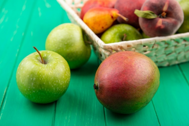 녹색 표면에 양동이에 배 복숭아 같은 다른 과일과 녹색 사과의 전면보기