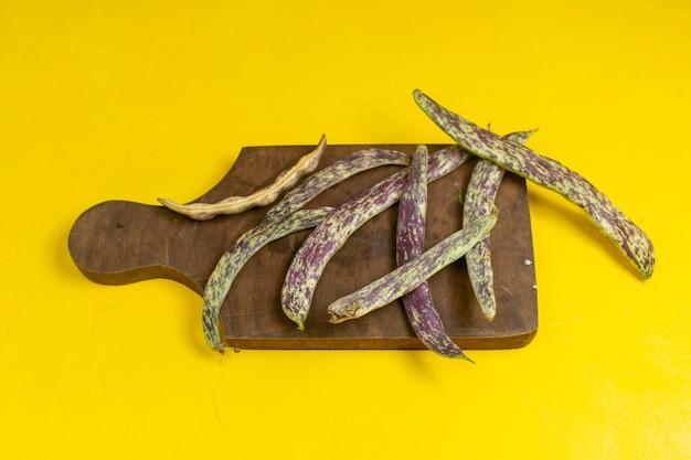 黄色の壁に緑の新鮮な豆生の長い植物豆の正面図