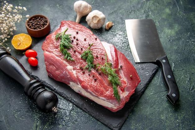 Вид спереди зеленого на свежее красное сырое мясо на разделочной доске и перец лимонный черный молоток цветочный топор на зеленом черном фоне цвета смеси