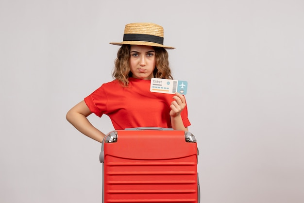 スーツケースを持っている不機嫌そうな休日の女の子の正面図