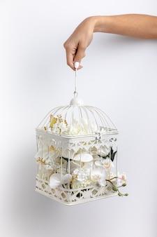 Вид спереди руки, держащей клетку для птиц, наполненную цветами