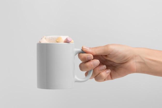 마쉬 멜 로우와 함께 크리스마스 머그잔을 들고 손의 전면보기