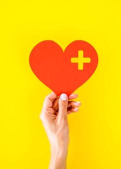 Вид спереди руки, держащей бумажное сердце на всемирный день сердца
