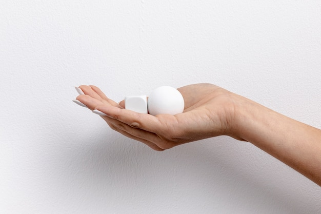 Вид спереди руки, держащей маленький куб и мяч