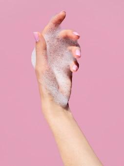 石鹸からの泡を持つ手の正面図