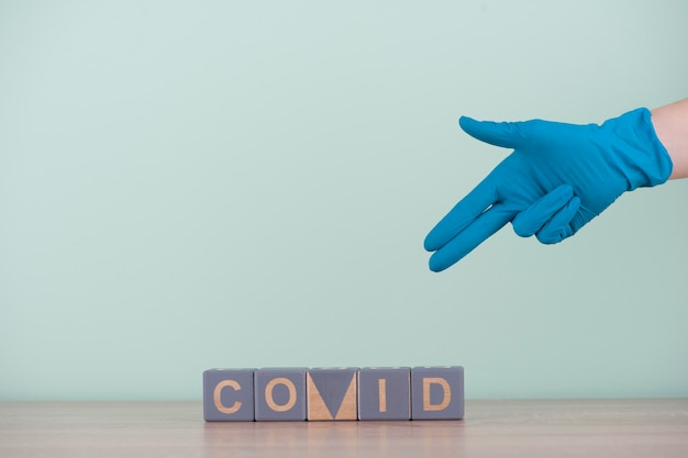 Вид спереди руки с хирургической перчаткой и деревянными кубиками с covid