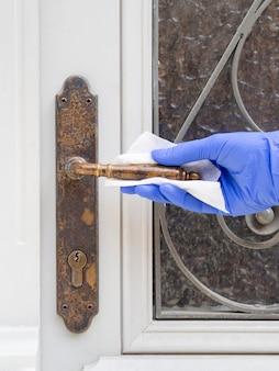 外科用手袋のドアハンドルをクリーニングする手の正面図