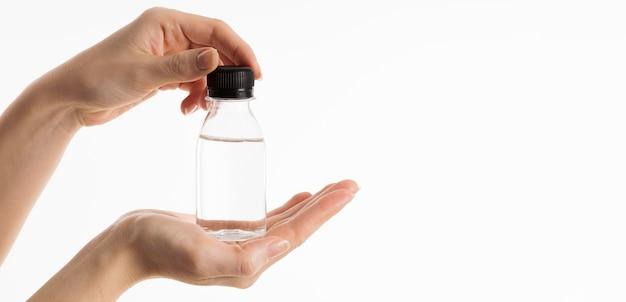 액체의 병을 들고 손의 전면보기