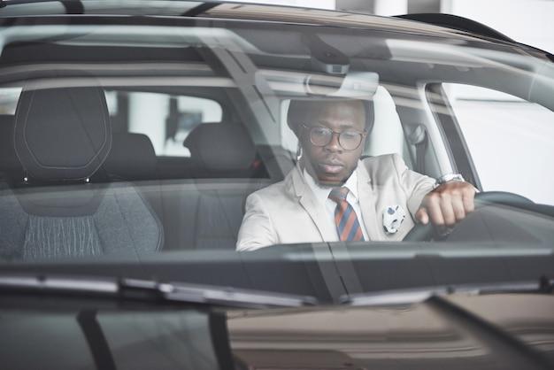 ハンサムなアフリカのエレガントな深刻なビジネスの男性の正面図は車を運転します
