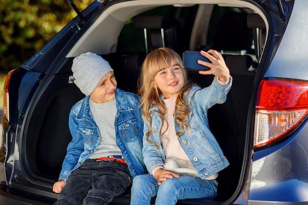 帽子でハンサムな男の子と彼女の電話で写真を撮るブロンドの長い髪のかわいい女の子の正面図