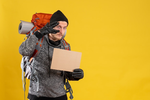 Вид спереди красивого мужчины-туриста с кожаными перчатками и рюкзаком с пустым картоном
