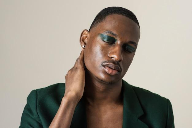 ブレザーでポーズをとって化粧をしているハンサムな男の正面図
