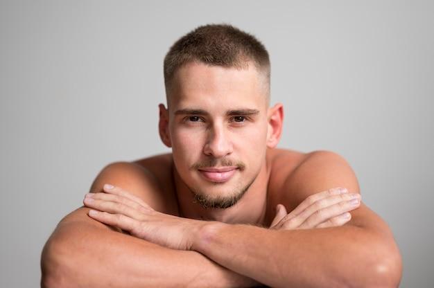 Вид спереди красивого мужчины, позирующего без рубашки со скрещенными руками
