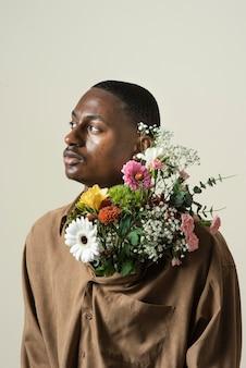 Вид спереди красивого человека, позирующего с букетом цветов
