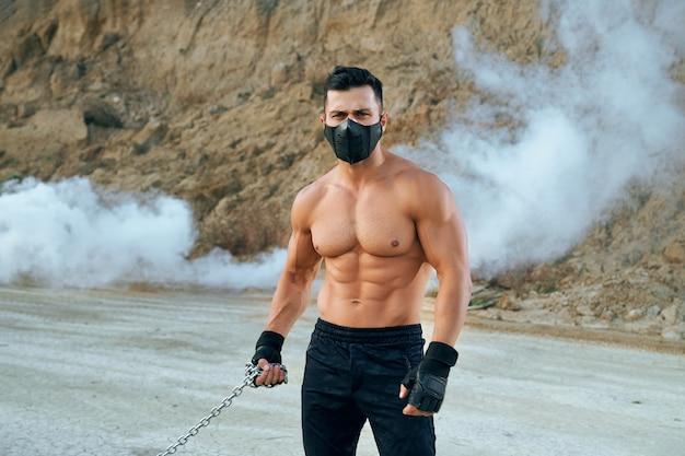 砂場に立っている間、手に金属チェーンを保持している運動体を持つハンサムな男の正面図。スポーツパンツ、手袋、医療用保護マスクを着用した筋肉質の男性。
